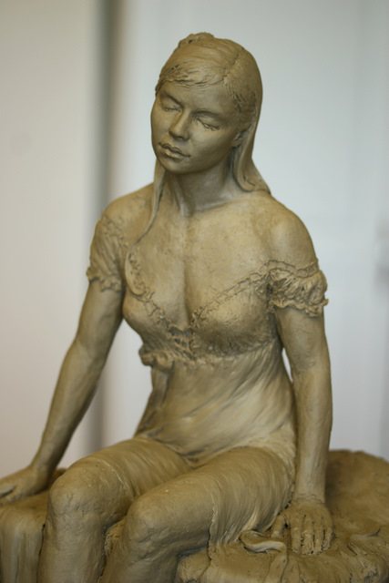 Closeup of woman resting on the grass sculpture.