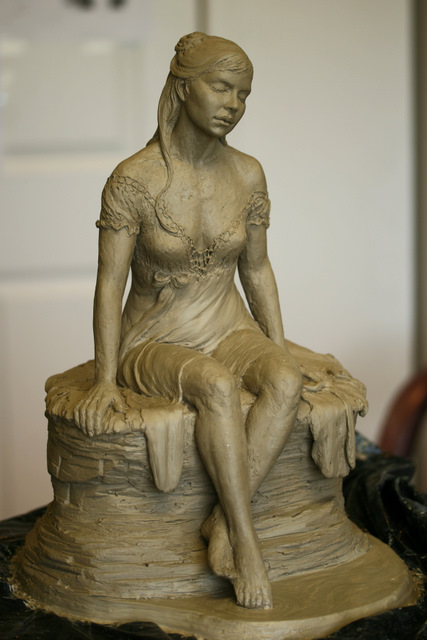 Front view of woman putting her toes in the water sculpture.