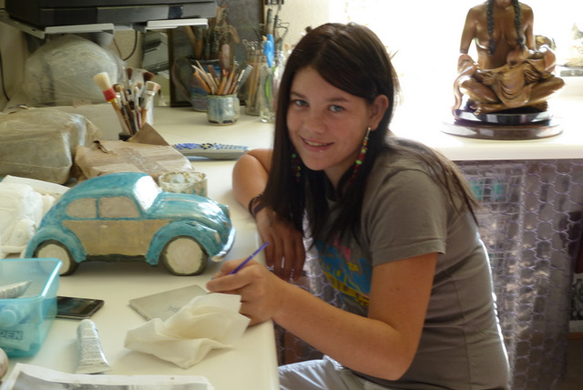 Tristyn paiting the chrome unto her fired ceramic car.