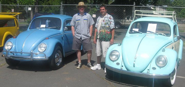 David and his buddy Tim at a car show showing off their Volkswagen bugs.