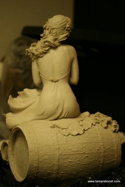Back view of unfired clay lady sculpture.