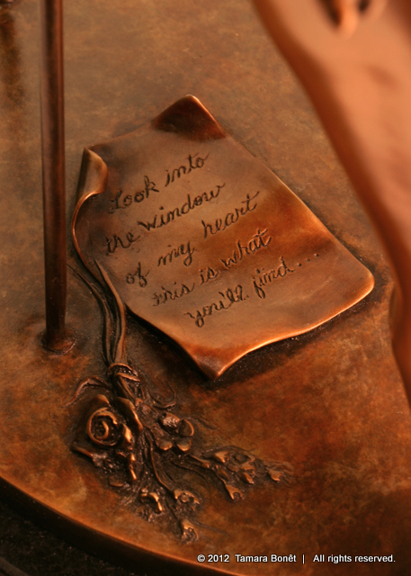 """Look into the window of my heart, this is what you'll find"" note in bronze."