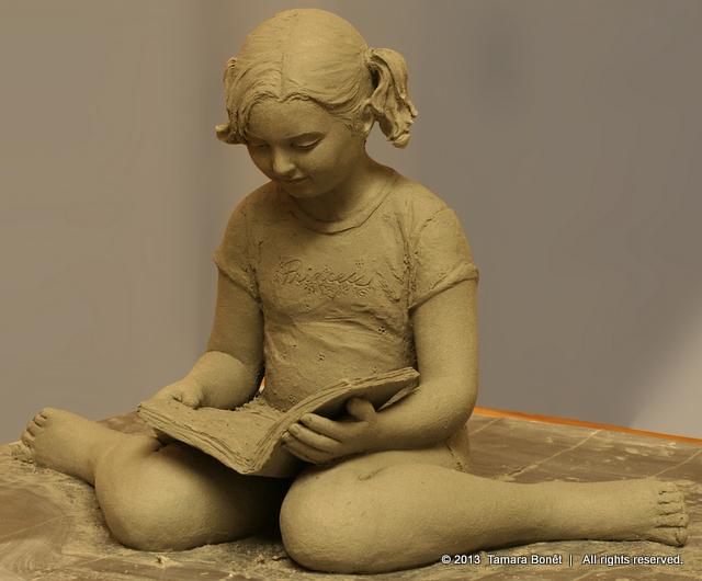 Little girl reading a book sculpture.
