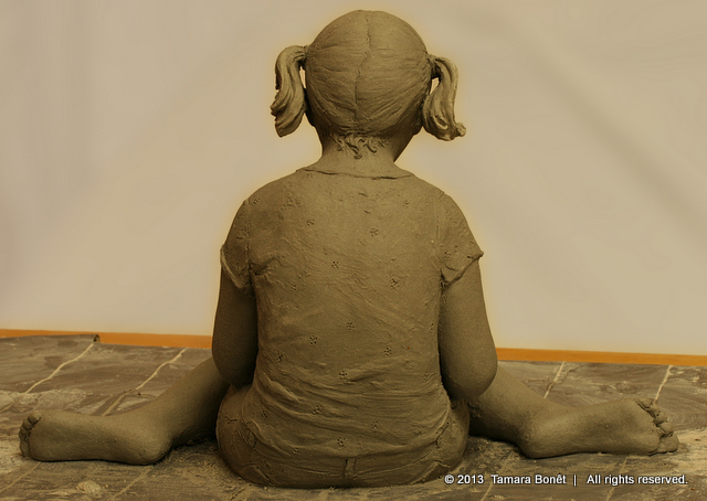 Back view of the girl with pigtails reading her book. Sculpture