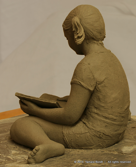 Young girl likes perusing her children's book and soaking it up. Book Sculpture.